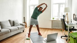Personal trainer. Full length shot of male fitness instructor stretching his body while streaming, broadcasting video lesson on training at home using laptop. Sport, online gym concept. Web Banner