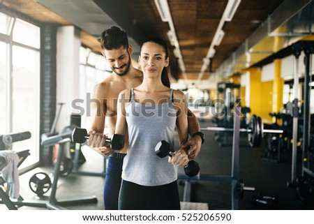 Personal trainer giving instructions to student  in gym