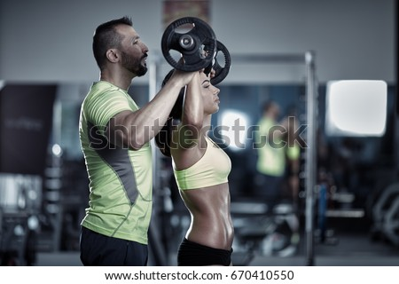personal trainer helping a...