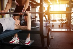 Personal trainer helping woman bench press in gym