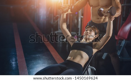 Personal trainer helping woman bench press in gym, Training with barbell, Personal trainer helping woman working with heavy dumbbells, Fitness instructor exercising with his client at the gym.