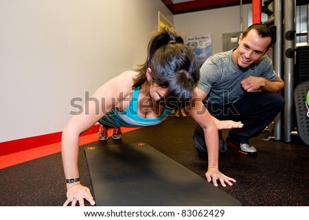 Personal Trainer helping woman do pushups.