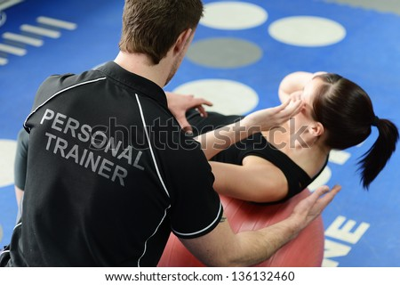 personal trainer helping young...