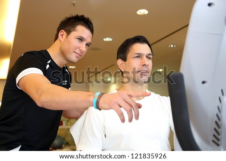 Personal trainer in a gym showing athletic man the training bike