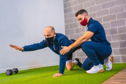 Personal trainer in the gym correcting the stretching of the student on the floor in the coronavirus pandemic, a new normal. With protective face mask