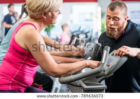 Personal trainer instructs senior woman about spinning at the gym