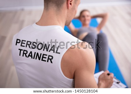 Personal Trainer Looking At Young Woman Doing Exercise On Yoga Mat
