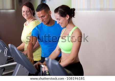 Personal trainer setting treadmill for a couple of young women
