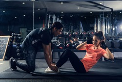 Personal trainer to practice sit-ups in the gym