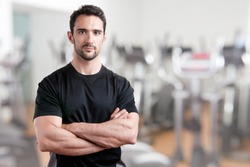 Personal trainer with is arms crossed, in a gym