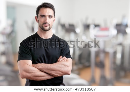 Personal trainer with is arms crossed, in a gym Stock photo ©