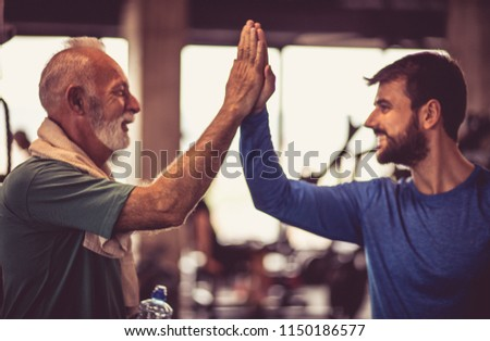 Personal trainer with senior man at gym. Close up.