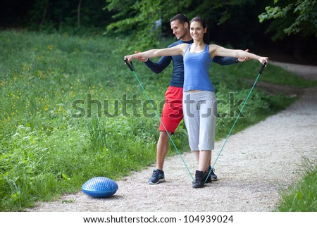 Personal trainer working with his client, helping her with execution of shoulder exercise