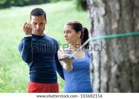 Personal trainer working with his client, showing her how to properly execute the exercise with resistance band