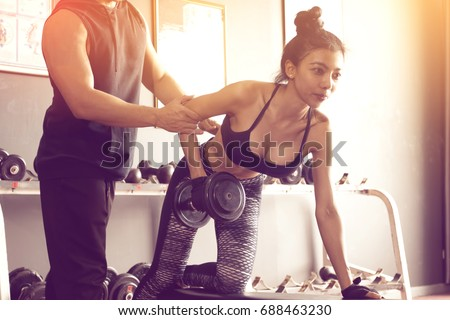 Personal training men help women's arms to pull up dumbbell for exercise at indoor gym.