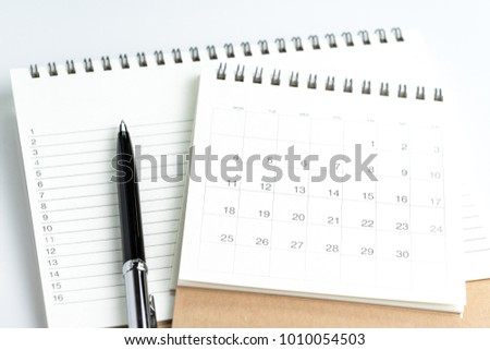 Personal yearly to do lists or new year's resolution or plan concept by clean calendar and  list of numbers on white notepad with pen