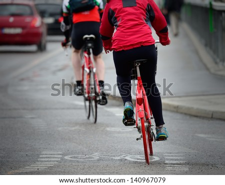 Persons on bikes seen from behind, in rain