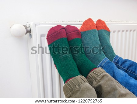 Persons, wearing warm wooly socks, warming feet in front heater. Conceptual image of home heating. #1220752765