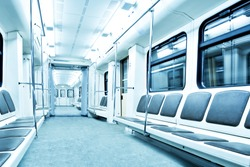 Perspective and diminishing wide angle view to Contemporary blue spacious interior and comfortable seats of modern train empty light illuminated wagon moving fast inside urban vanishing metro tunnel