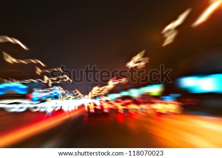 Perspective and panoramic wide angle view of modern light blue illuminated and spacious high-speed urban road and moving cars with fast blurred trail of headlights in vanishing traffic motion at night