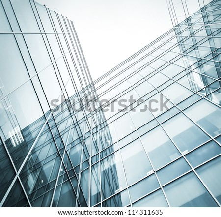 Perspective and underside angle view to textured background of contemporary glass building skyscrapers at night