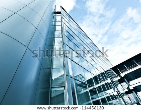 Perspective and underside angle view to textured background of modern glass building skyscrapers over blue cloudy sky #114456130