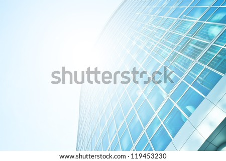 Perspective and underside angle view to textured background of modern glass building skyscrapers over blue bright clear sky with sunlight
