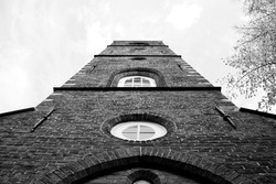 Perspective from below an old, brick church steeple in Amsterdam.