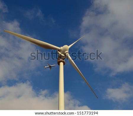 Perspective image from below of towering wind turbine and aircraft flying above, on blue sky with clouds background