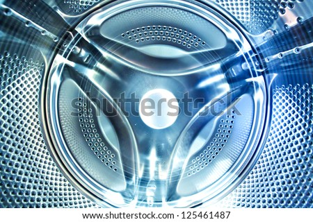 Perspective inside view into blue washing machine drum moving in fast and quick traffic motion blur