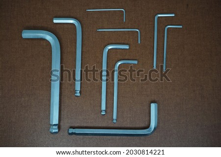 Perspective L-Shaped Hex Wrench set isolated on brown background. Stock fotó ©