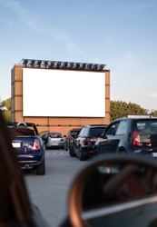Perspective of a cinema drive in parking with cars parked in front of a big white screen to watch movies or films inside the car. Open air public Cinema drive-in. Social Distance, covid-19
