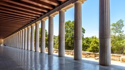 Perspective of classical building columns in ancient Agora, Athens, Greece. Panoramic view inside the Stoa of Attalos, landmark of Athens. Historical architecture of Athens city. Repetition concept.
