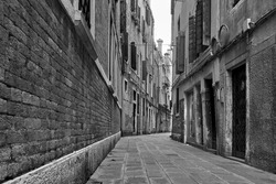 Perspective of empty street in Venice, Italy. Black and white urban photography