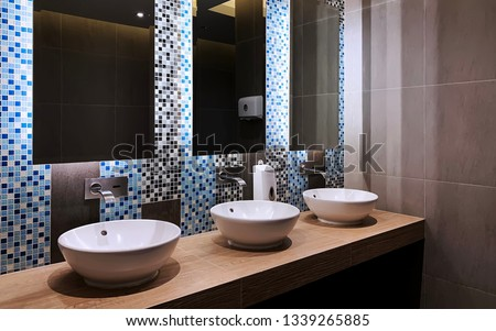 Perspective of hand wash bar with mirror glass and wash basins in a restroom