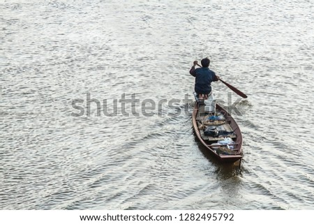 perspective of High angle view of one person or Thai man. alone on boating with oar at Chi river ripple water texture of Thailand. livelihood of life living as fisherman. with copy space.