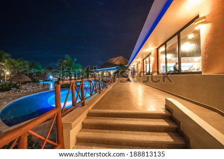 Perspective of promenade between swimming pool and a restaurant at a luxury caribbean resort at night, dawn time. Bahia Principe, Riviera Maya, Mexico. - Shutterstock ID 188813135
