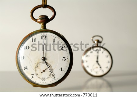perspective of two old clocks at five o\'clock