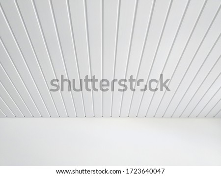 Photo of  Perspective of white wood sheeting ceiling and smooth white wall in Caribbean construction. White ceiling beams pattern background.