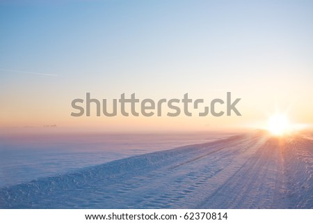 Perspective of winter road on sunset