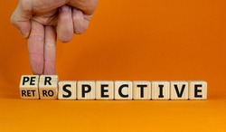 Perspective or retrospective symbol. Businessman hand turns cubes and changes word 'retrospective' to 'perspective'. Beautiful white background. Business and perspective concept. Copy space.