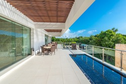 Perspective, outlook at the modern stylish restaurant, cafe, bar on the balcony, deck, patio of the luxury Mexican resort. Exterior, interior design.