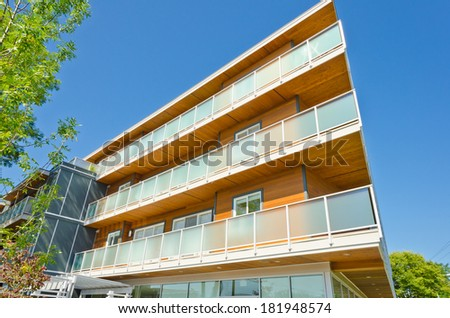 Perspective, outlook of the modern glass, wood and steel building, house with the balconies on perimeter.  Exterior design.