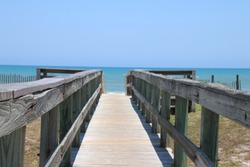 Perspective photograph of wooden walkover bridge to beach on sunny blue sky day with turquoise water and no clouds on the horizon.