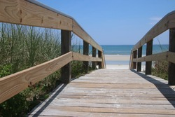 Perspective photography of wooden boardwalk walkover bridge to beach with turquoise blue ocean water on horizon.
