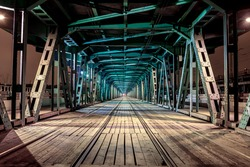 Perspective rail bridge by night. Vanishing point Gdanski tram bridge in Warsaw, Poland. Colorful game of shadow and light