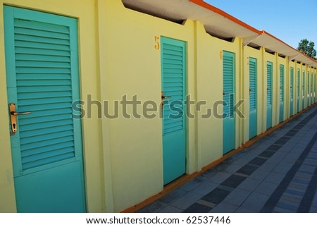 Perspective row of turquoise and yellow beach huts, Rimini, Italy