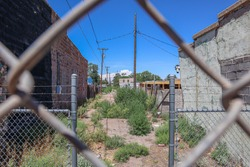 Perspective Shot Of An Alley in Holbrook Arizona Through Chain Link Fence