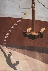 Perspective side view of the old rusty anchor with draft mark numbers on fore side of large vessel hull in vertical frame
