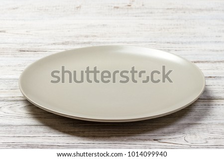 Perspective view. Empty white plate on wooden background.